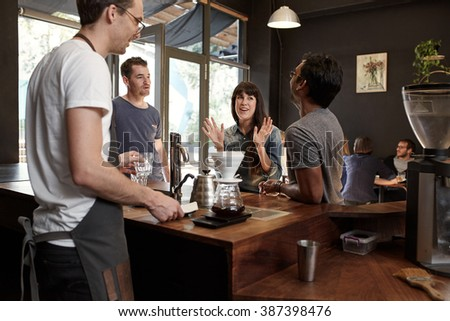 Woman gesturing while talking with colleagues at coffee shop - stock photo