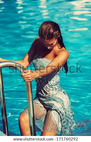 woman get out from the pool wearing blue dress - stock photo