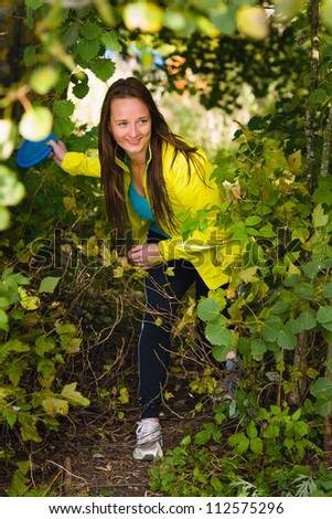 Woman get ready to throw a disc out the bush, vertical format - stock photo