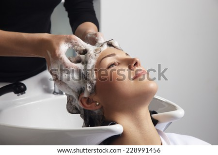 woman getting a hair wash procedure in salon - stock photo