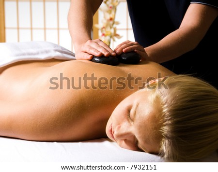 woman getting a hot stone massage at a day spa - stock photo