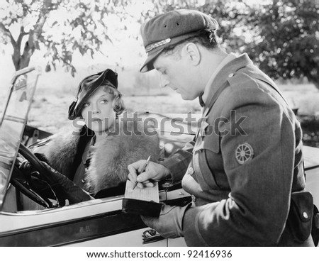 Woman getting a ticket from a policeman - stock photo
