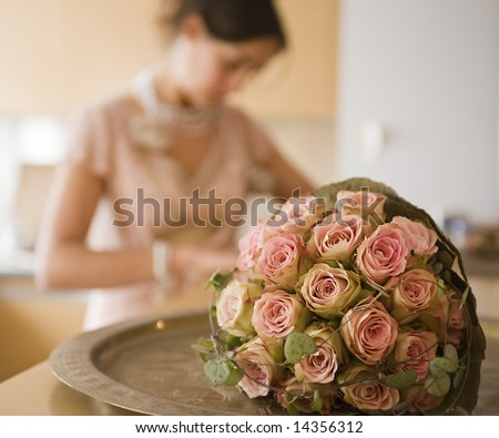 woman getting dressed for wedding. Focus on wedding bouquet. - stock photo