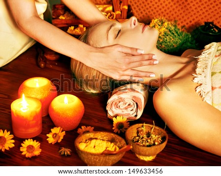 Woman getting facial massage in tropical beauty spa.