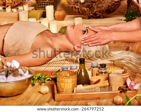 Woman getting facial massage in tropical beauty spa. Visible hand  - stock photo