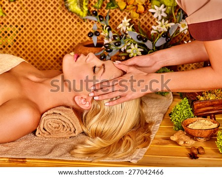 Woman getting facial massage in tropical spa. Hands on forehead - stock photo