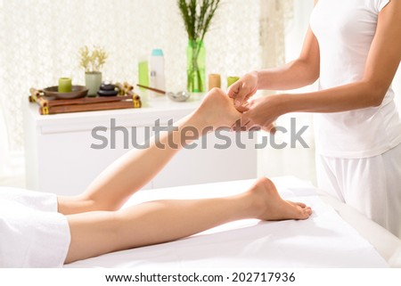 Woman getting feet massage in the spa salon - stock photo