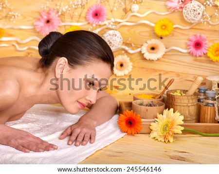 Woman getting herbal ball massage  in spa. - stock photo
