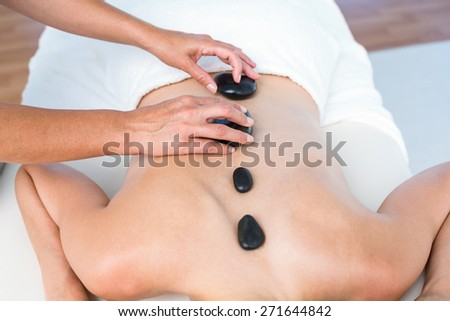 Woman getting hot stone massage in a healthy spa - stock photo
