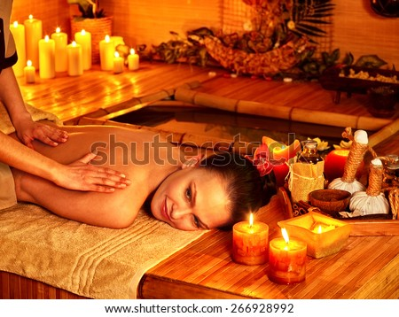 Woman getting massage in bamboo spa. Female therapist.