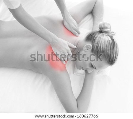 Woman getting massaging treatment over white background (black and white image with the red inflammation area) - stock photo