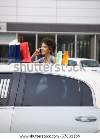 woman getting out of limousine with shopping bags. Vertical shape, copy space - stock photo