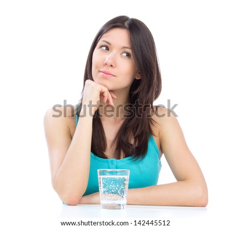 Woman getting ready to drink glass of water on the table. Healthy weight loss concept on a white background - stock photo