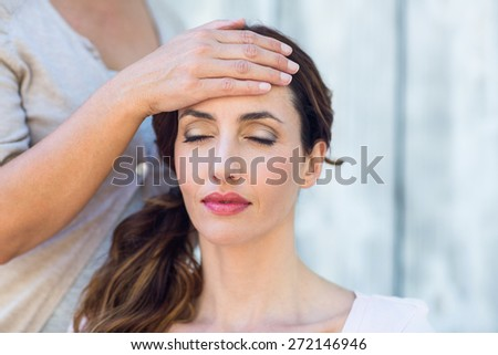Woman getting reiki therapy on wooden background - stock photo