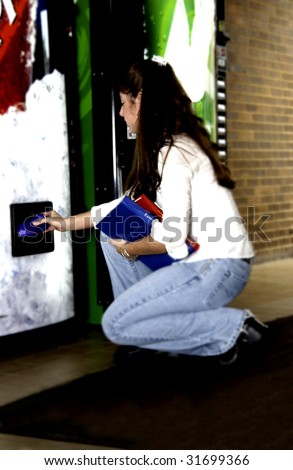 Woman getting soda from vend machine - stock photo