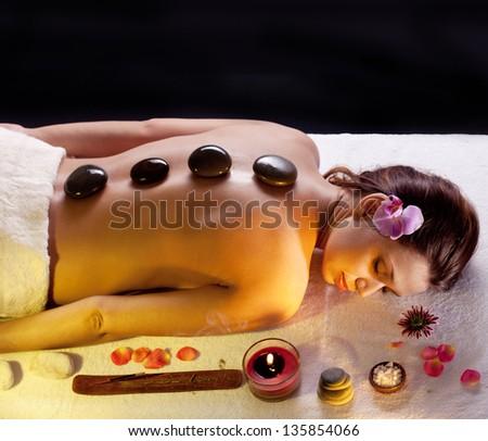 Woman getting stones spa procedures. - stock photo