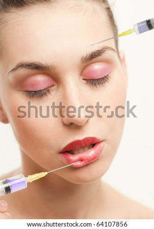Woman getting two injections of hyaluronic, collagen,HA injection in lips and at one's head - stock photo