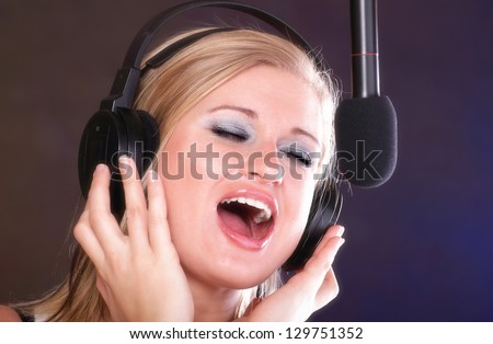 woman girl is singing rock song with a microphone headphones - stock photo