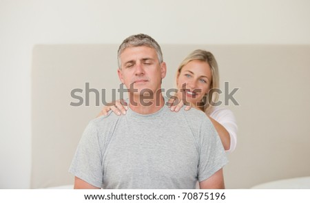 Woman giving a massage to her husband - stock photo