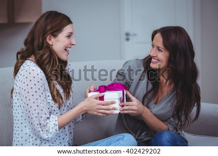 Woman giving a present to her friend in living room at home