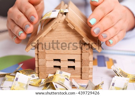 Woman giving a small home safety with her hands as a roof