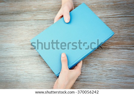 Woman giving book to woman, on wooden table background - stock photo