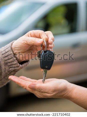 Woman giving car keys to another woman - stock photo