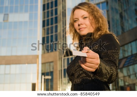 Woman giving credit card, or doing shopping and paying opposite office building