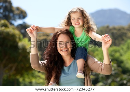 Woman giving daughter a piggyback