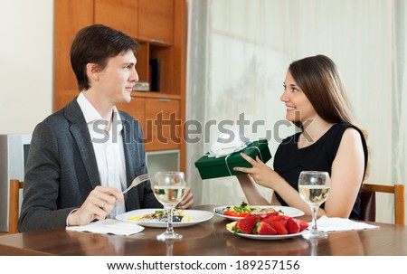 Woman  giving gift  to man at table during romantic dinner - stock photo