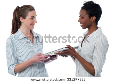 Woman giving laptop to her friend - stock photo
