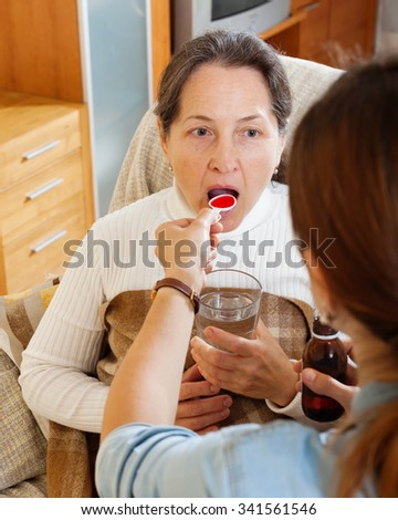Woman giving medicinal syrup to mature mother at home - stock photo