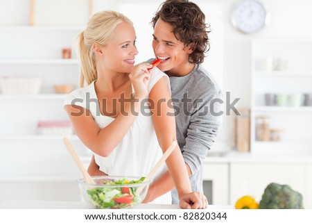 Woman giving pepper to her fiance in their kitchen - stock photo