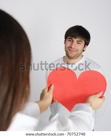 Woman giving to young man love symbol