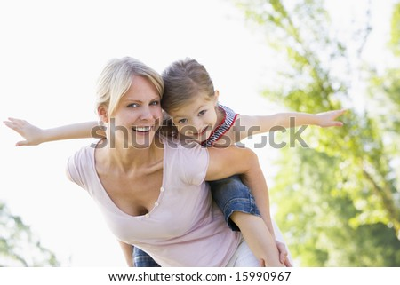 Woman giving young girl piggyback ride outdoors smiling - stock photo