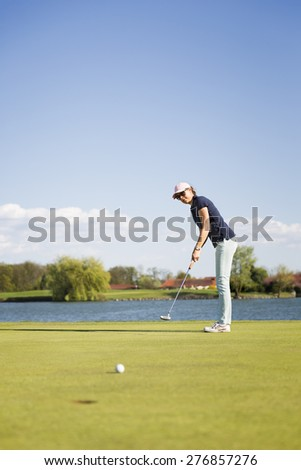 Woman golf player putting on green with lake in background, with empty copyspace. - stock photo