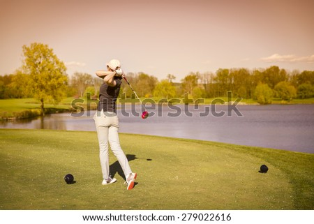Woman golf player swinging golf club from tee box at dusk. - stock photo