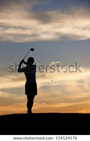 Woman golfer hits ball.