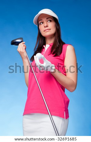 Woman golfer holding a driver and golf ball - stock photo