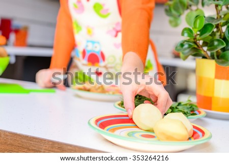 Woman grab peeled potato by hand,in modern kitchen