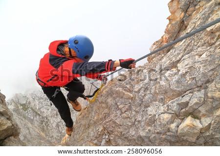 "Woman grabbing the protection cable on vertical ridge along via ferrata ""Punta Ana"", Tofana massif, Dolomite Alps, Ital - stock photo"