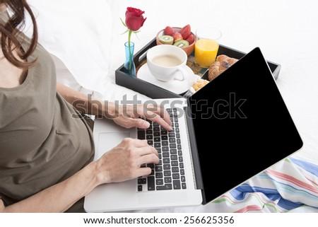 woman green shirt striped pajama pants sitting on white bed typing keyboard laptop with breakfast tray croissants orange juice strawberry kiwi cupcake red rose flower - stock photo