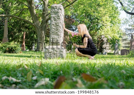 Woman grieving at headstone in cemetery for grief or loss concept - stock photo