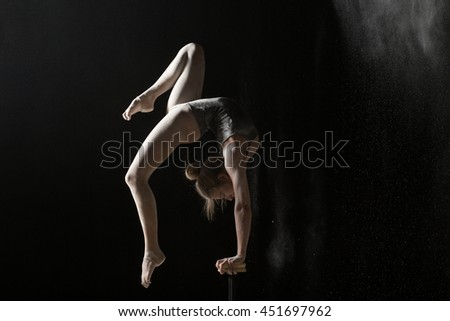 Woman gymnast handstand on equilibr at black background - stock photo