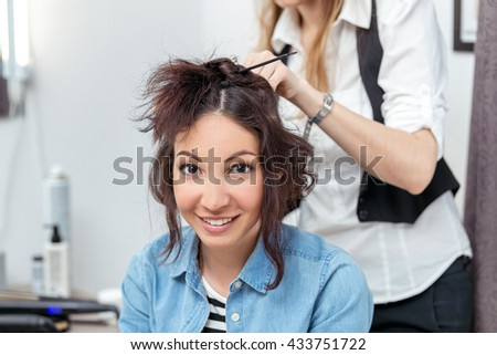 Woman hairdresser making hairstyle using curling iron for long hair of young female in beauty salon - stock photo