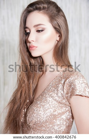 WOMAN-haired, she is dressed in a gold dress, her face a perfect trendy makeup