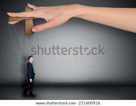 Woman hand control business man - stock photo