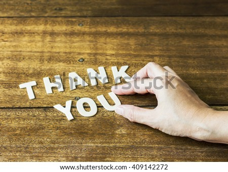 "woman hand design word ""Thank You""  by white letter press on wooden table, concept - stock photo"