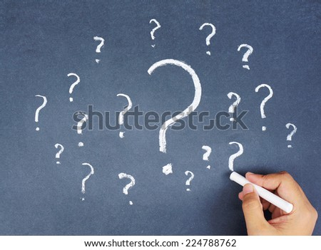 Woman Hand drawing lots of question marks on chalkboard - stock photo