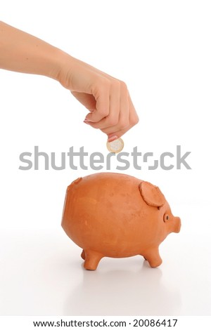 woman hand dropping coin in piggy bank against white - stock photo
